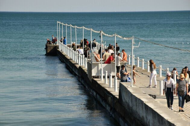 На волнорезах у моря люди гуляют группами.