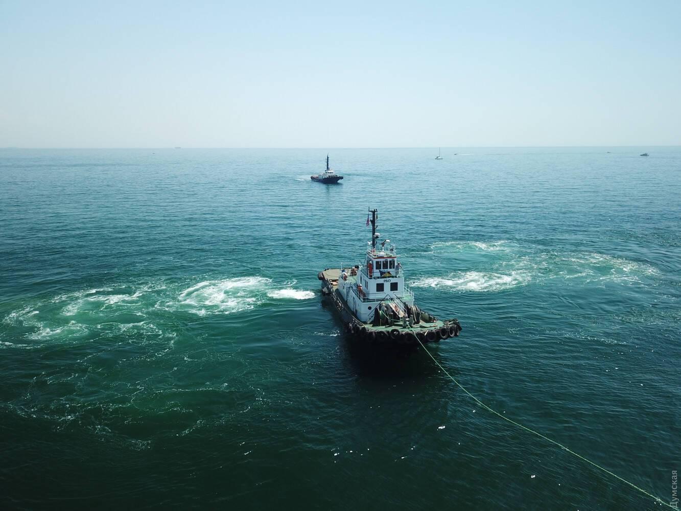 На буксиры завели тросы, чтобы дернуть затонувший танкер