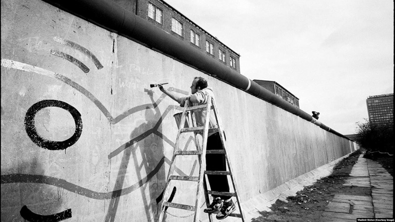 Американский художник Кит Харинг рисует на западной стороне Берлинской стены, 1986 год
