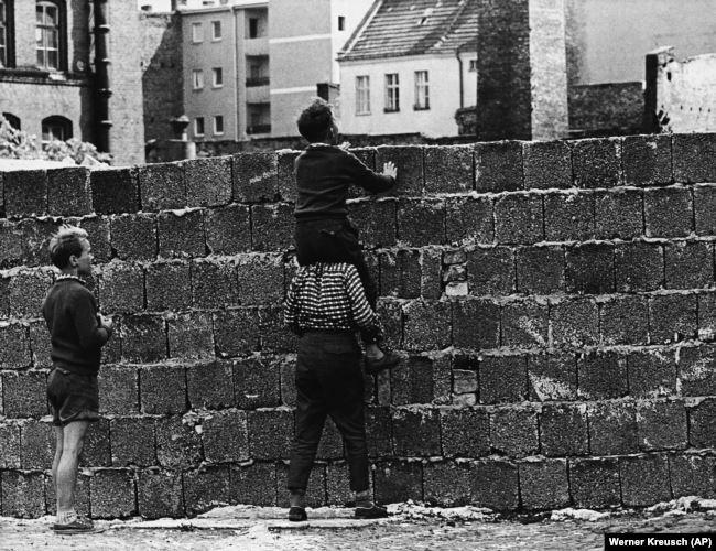 Район Веддинг в Западном Берлине 23 августа 1961 года. Мальчишка на плечах своего товарища смотрит через стену на кварталы в Восточном Берлине