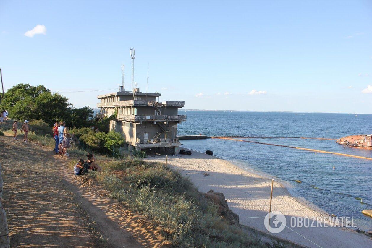 Сам корабель лежить на хвилерізі, а за ним із боку моря стоять камені