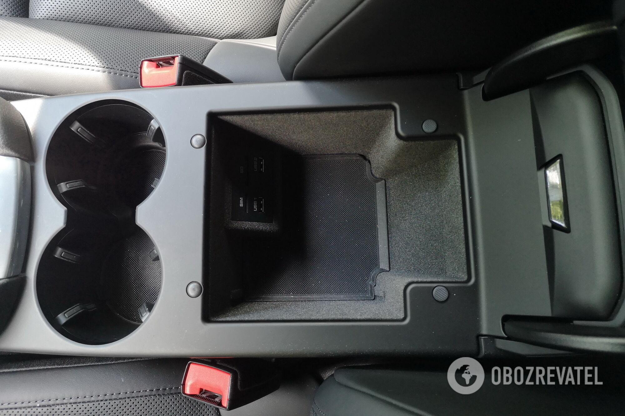 В подлокотнике между передники креслами есть глубокое отделение для мелочей, два подстаканника и порты USB и слот для SIM-карты. Фото: