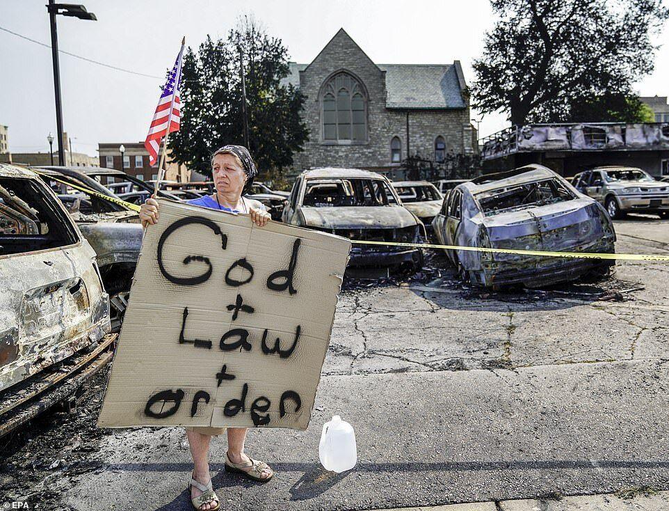 """Жінка поряд зі згорілими авто тримає прапор США і табличку з написом: """"Бог + закон + порядок"""""""