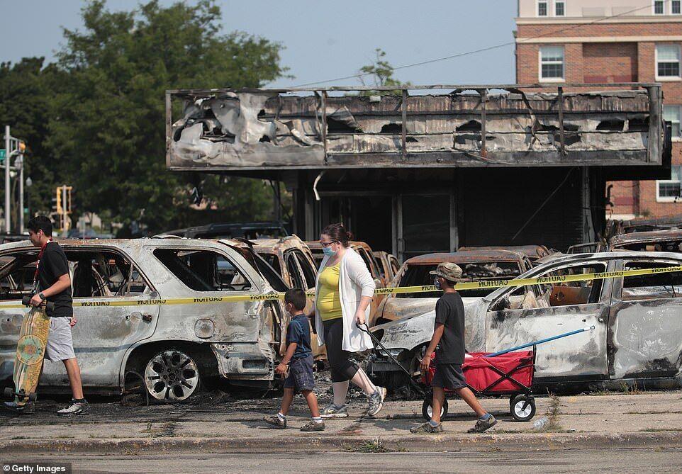Люди проходять повз згорілі автомобілі після ночі заворушень у Кеноші