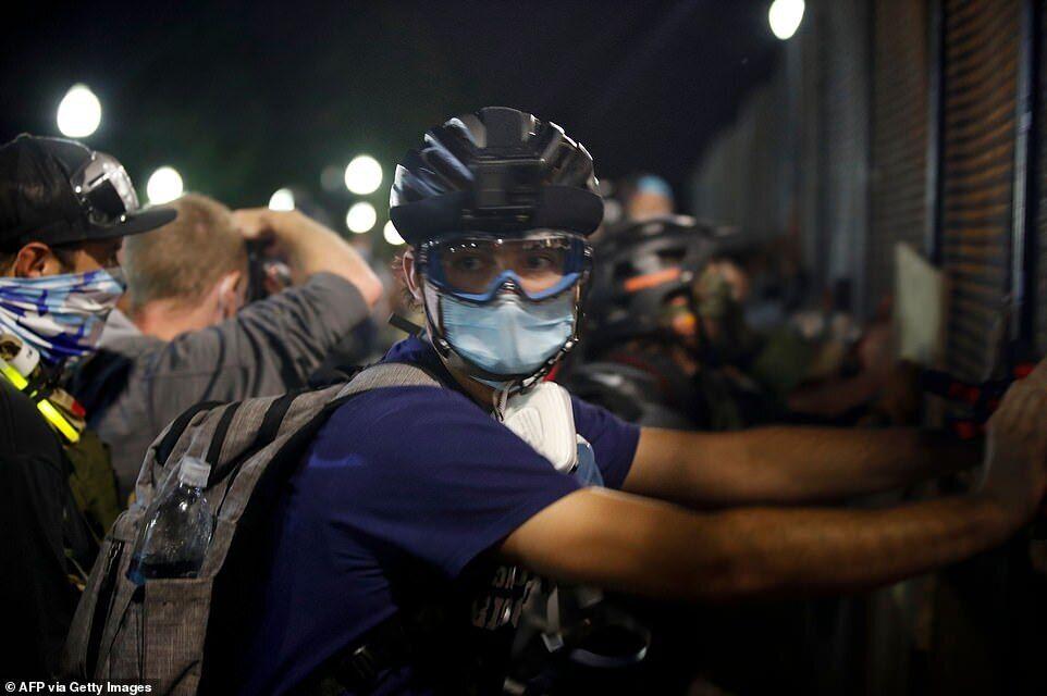 Протестующие собрались в шлемах и масках, а некоторые держали импровизированные щиты, готовясь к встрече с полицией