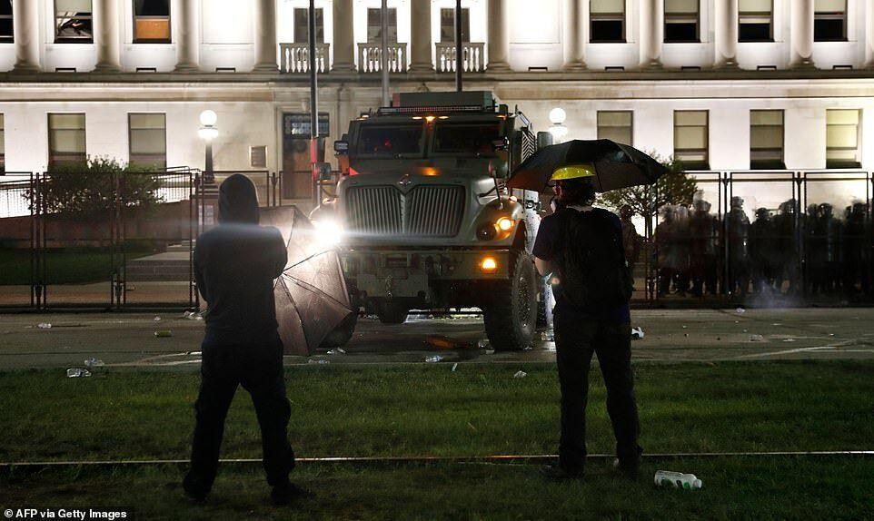 Бронированный автомобиль движется к внешней стороне железного забора перед зданием окружного суда, когда полиция стреляла слезоточивым газом по протестующим
