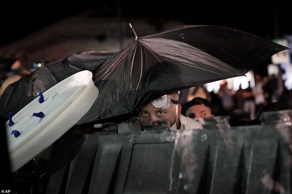 Протестующий прикрылся зонтиком и укрылся за мусорным контейнером во время столкновений у здания суда округа Кеноша