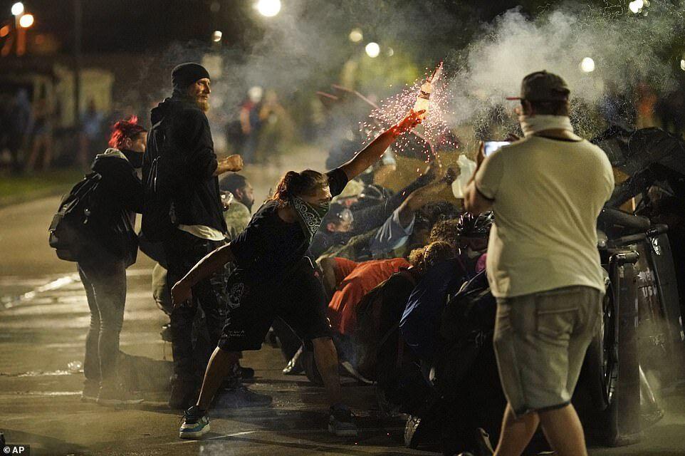 Протестующий бросает какой-то предмет в полицию, когда копы применили слезоточивый газ и другие боеприпасы для борьбы с массовыми беспорядками