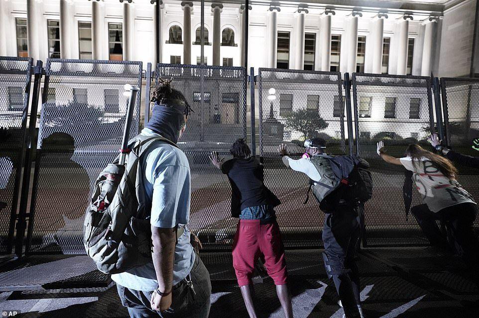 Демонстранты пытались пробраться через черный забор, установленный вокруг суда ранее, поскольку официальные лица готовились к новой ночи беспорядков