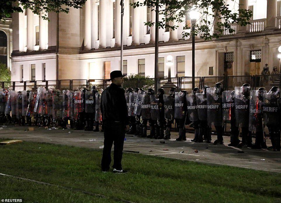 Мужчина стоял перед сотрудниками правоохранительных органов, когда они готовились к столкновению с протестующими