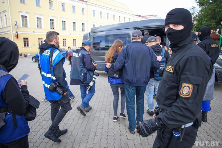 Силовики отвели граждан в микроавтобус.