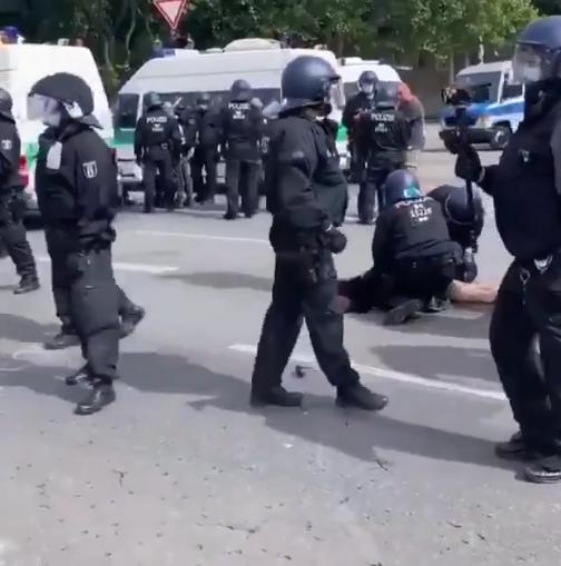 Женщина лежит на земле, окруженная полицейскими.