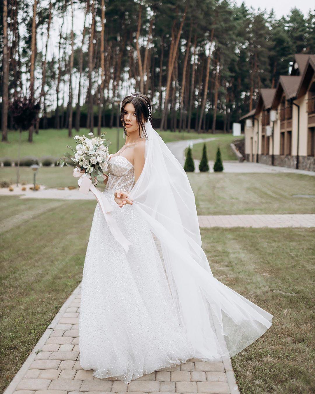 Мария Русина с букетом и в платье