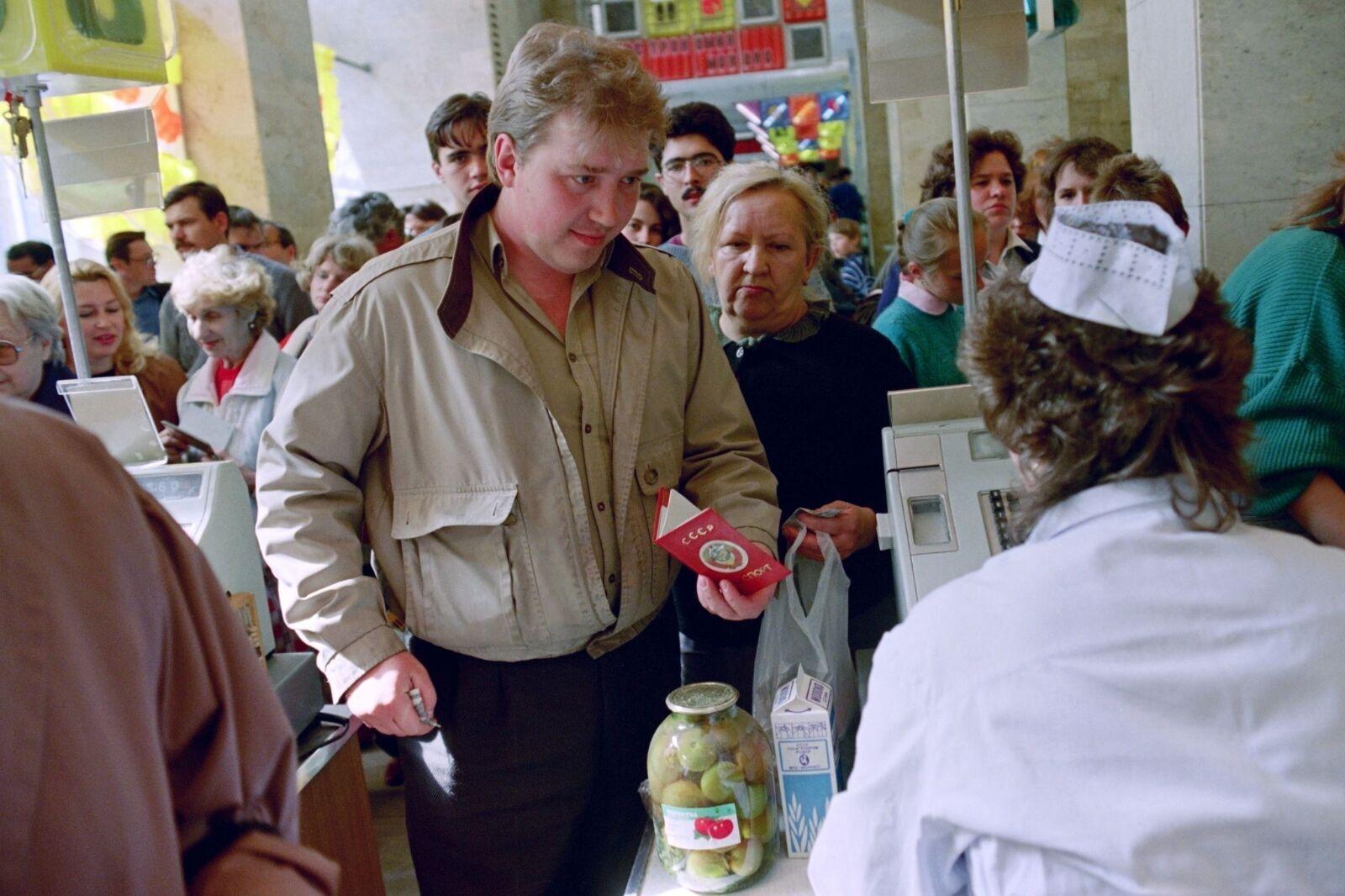 Мужчина показывает кассиру паспорт с московской пропиской, чтобы купить дефицитный товар