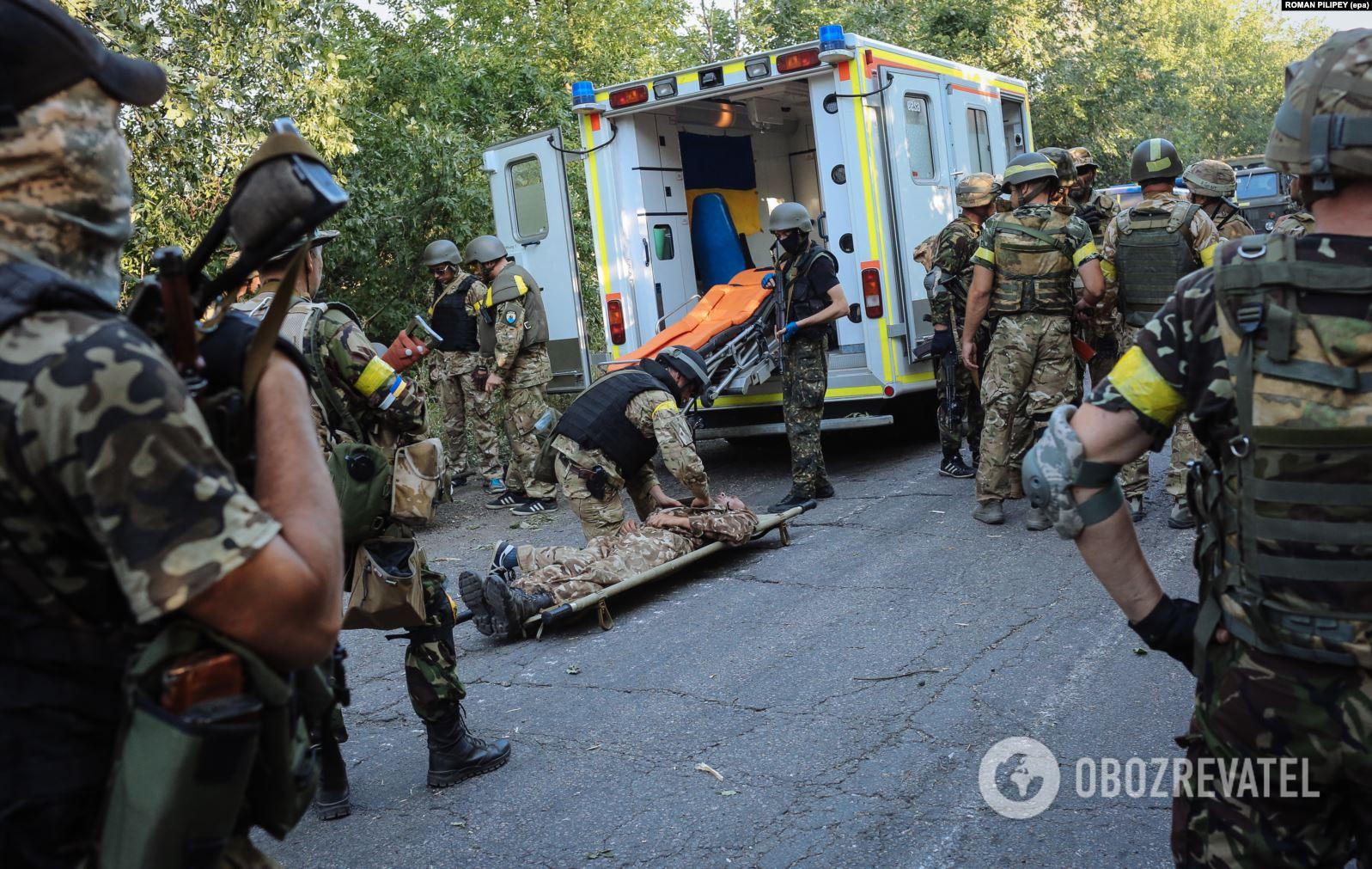 Українські бійці рятують товариша, пораненого поблизу Іловайська 10 серпня 2014 року