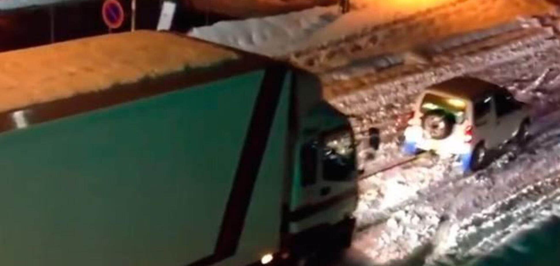Маленький автомобиль вытаскивает фуру из снега