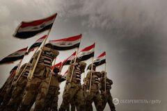 Иракские военные держат флаг Ирака