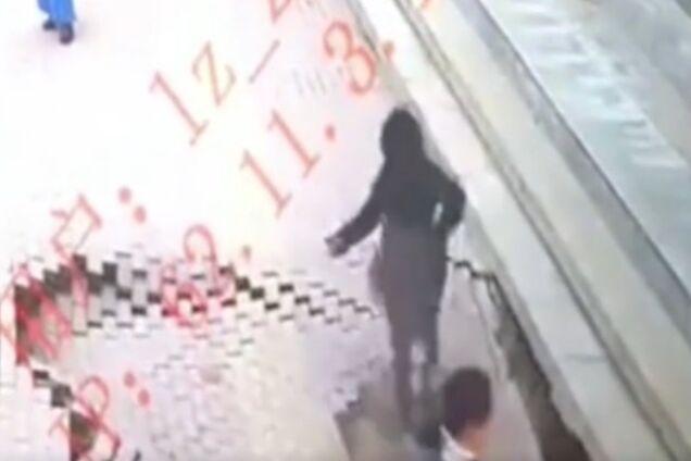 В Китае девушка провалилась под землю посреди улицы: момент попал на видео