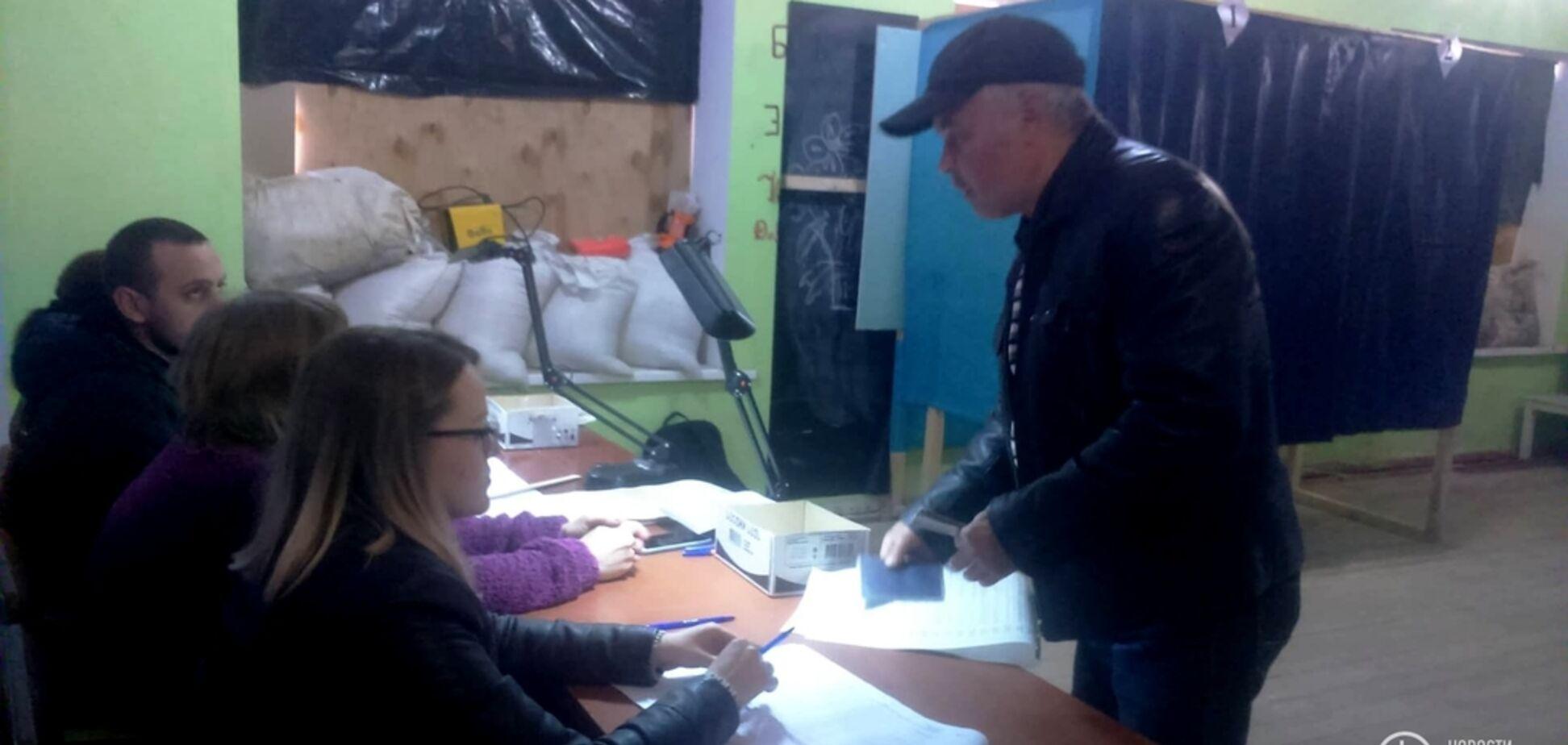 Мішки з піском і закриті фанерою вікна: як проходять вибори президента України на Донбасі