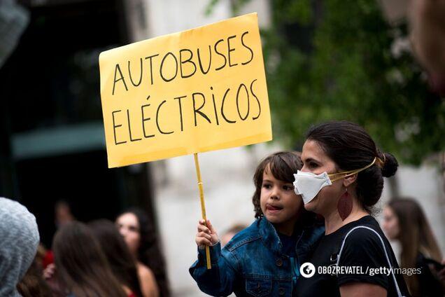 """Женщина и ребенок с плакатом """"электрические автобусы"""" во время забастовки в Гранаде, Испания"""