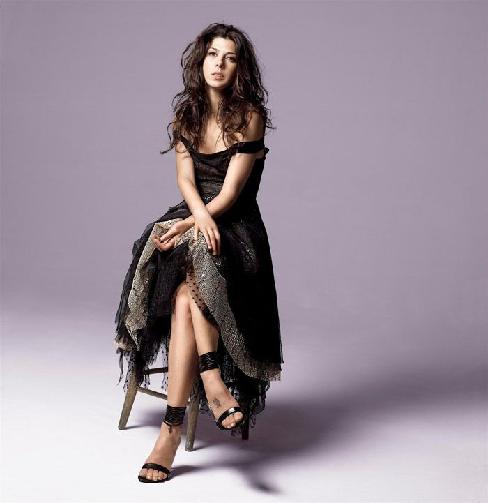 Мариса Томей в маленьком платье на большом табурете