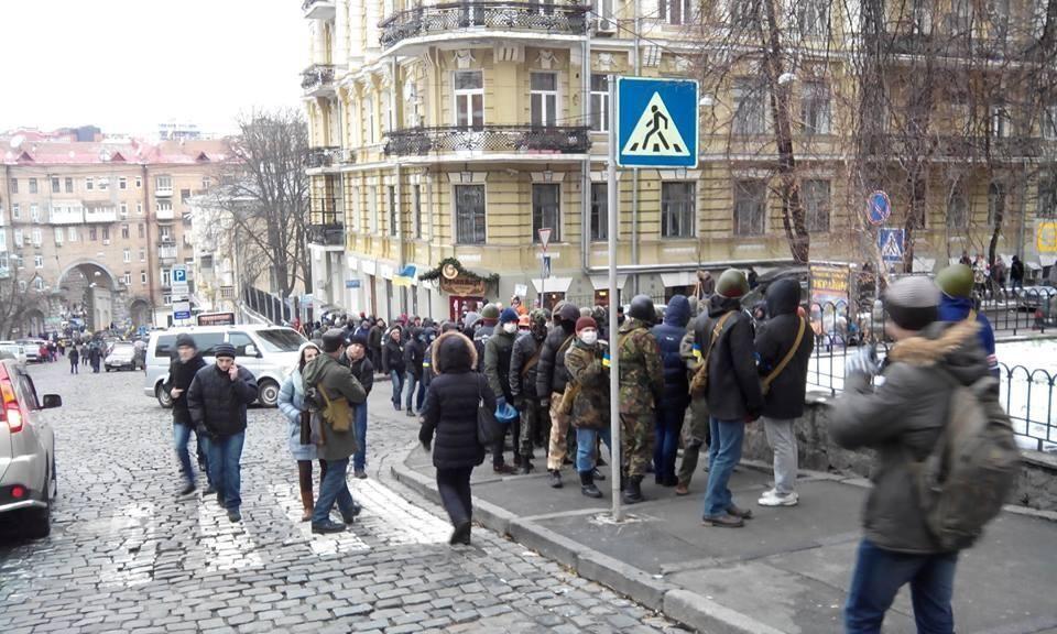 В сторону Администрации президента идет колонна парней в масках