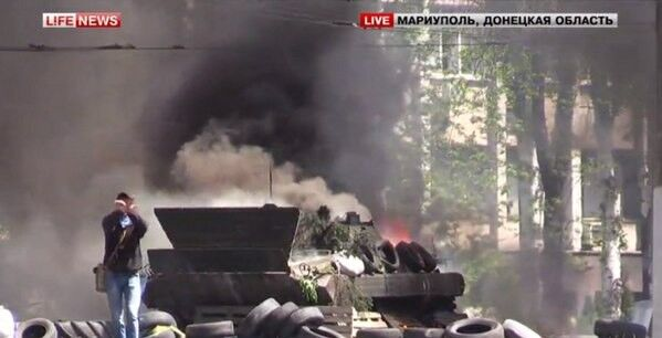 В центре Мариуполя - взрывы и выстрелы, горит БМП. Видеотрансляция