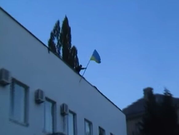 """В Ждановке оккупанты вместе с местными жителями """"дружно"""" топтали флаг Украины"""