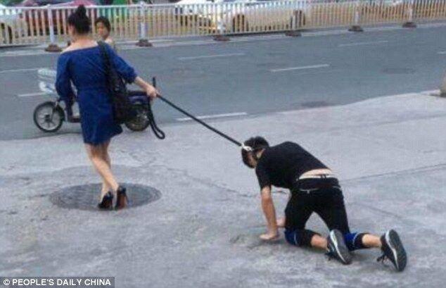 Китаянка пройшлася по вулиці з чоловіком на повідку
