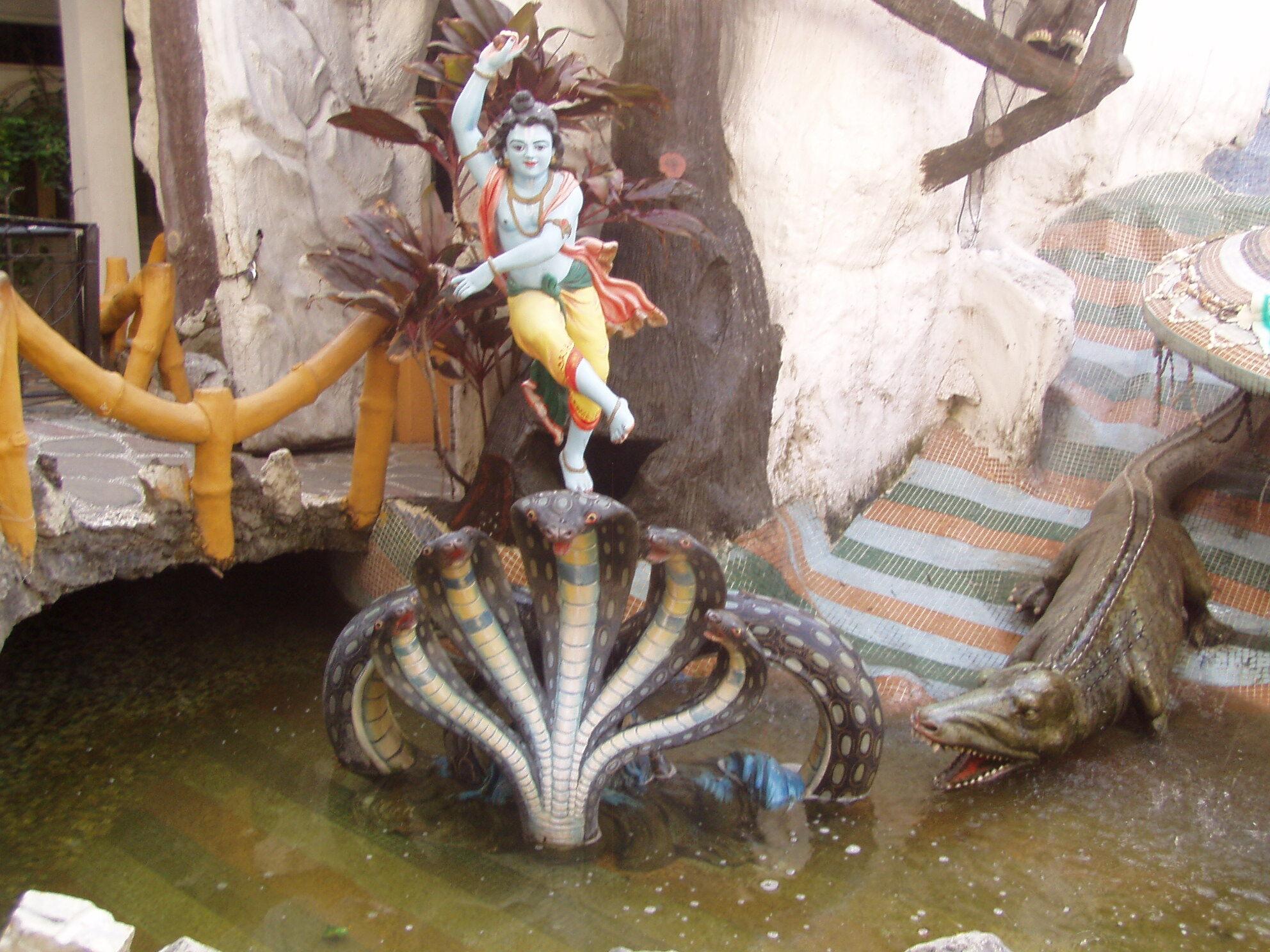 Синий Кришна в желтых штанах танцует на головах многоголового змея