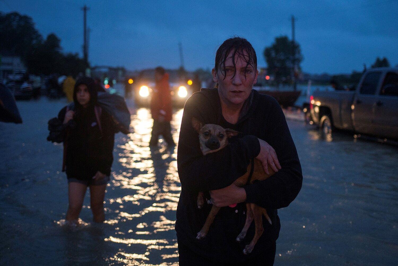Жінка тримає свою собаку після евакуації із будинку