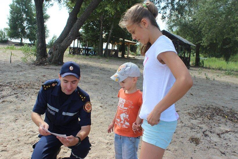 Спасатель рассказывает маме с ребенком о правилах поведения на воде