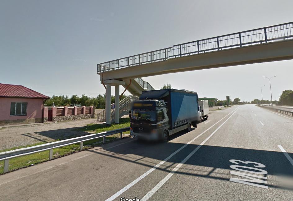 Место происшествия. На скриншоте Гугл. Карты 2015 года видно, что водители грузовиков нередко паркуются под мостом на обочине. В одну из таких машин и врезался MAN.