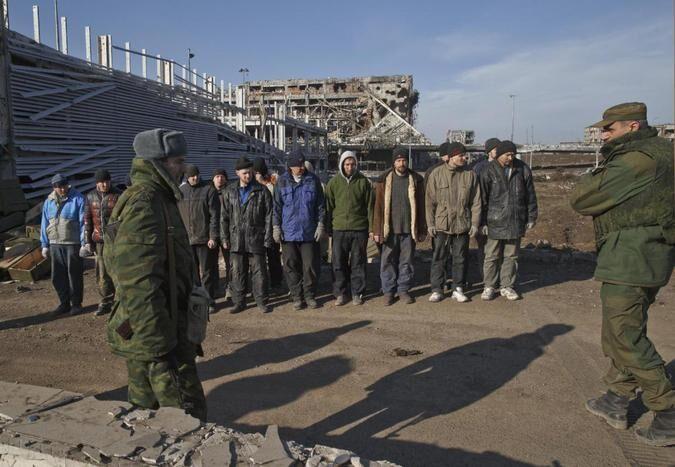 """Украинских военнопленных привезли искать тела """"киборгов"""" под завалами Донецкого аэропорта"""