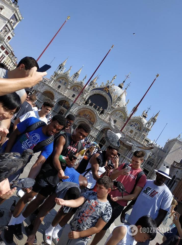 Туристы кормят ручных голубей на площади Сан-Марко в Венеции