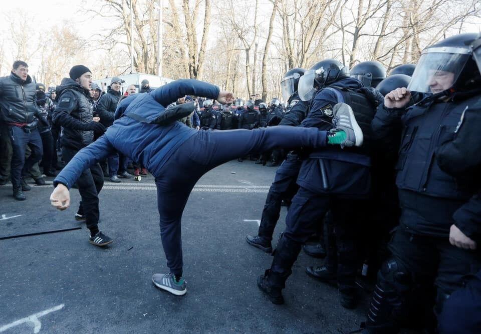 Мужчина удивительно высоко поднял ногу, замахнувшись перед правоохранителями
