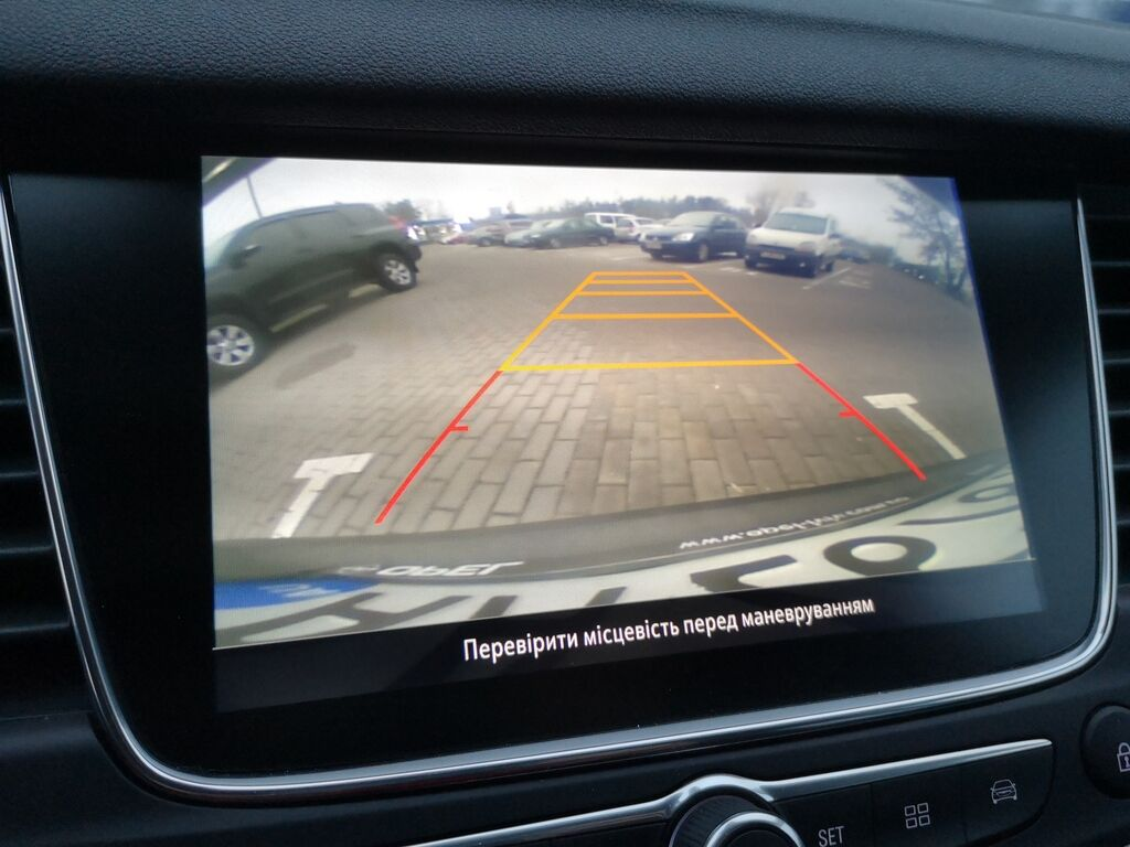 На центральный дисплей выводится изображение от опционной камеры заднего вида, но без динамических линий
