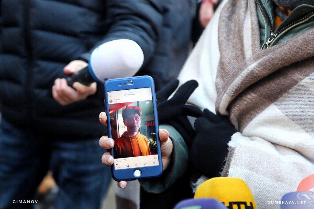 Девушка показывает фото своего пропавшего брата
