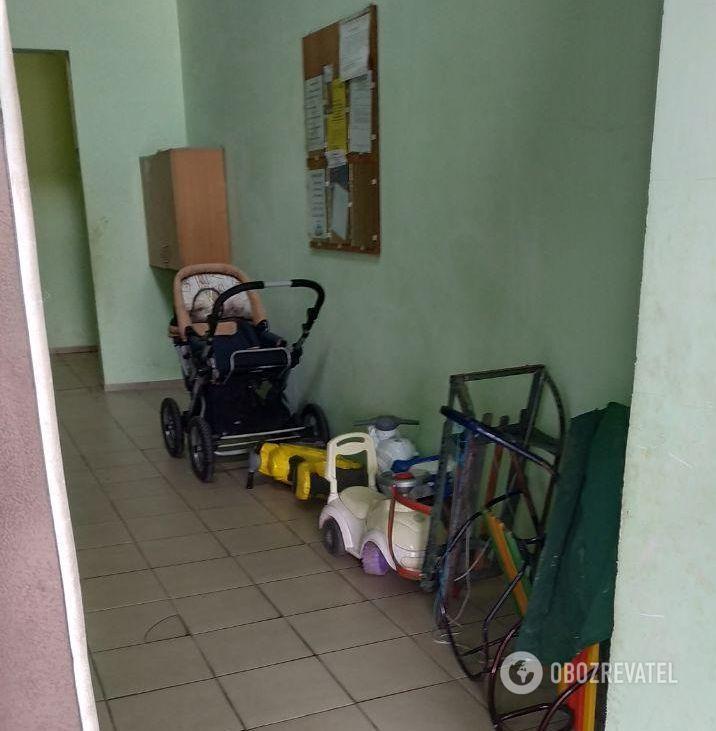В холле полно санок, колясок, игрушек — тут живут много детей
