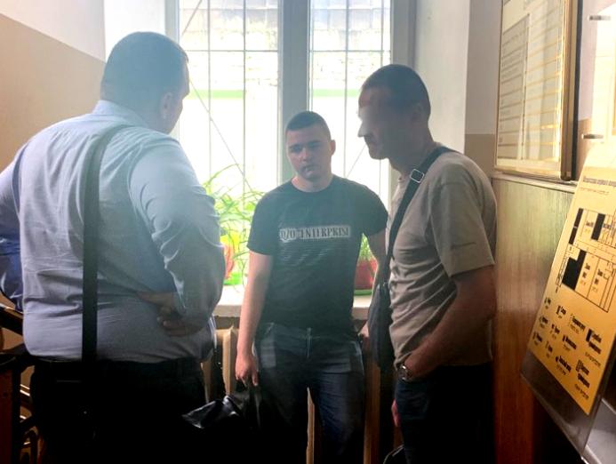 Підозрюваний (у центрі) перед початком суду