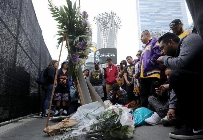 Шанувальники Кобі Браянта приносять квіти до його портретів