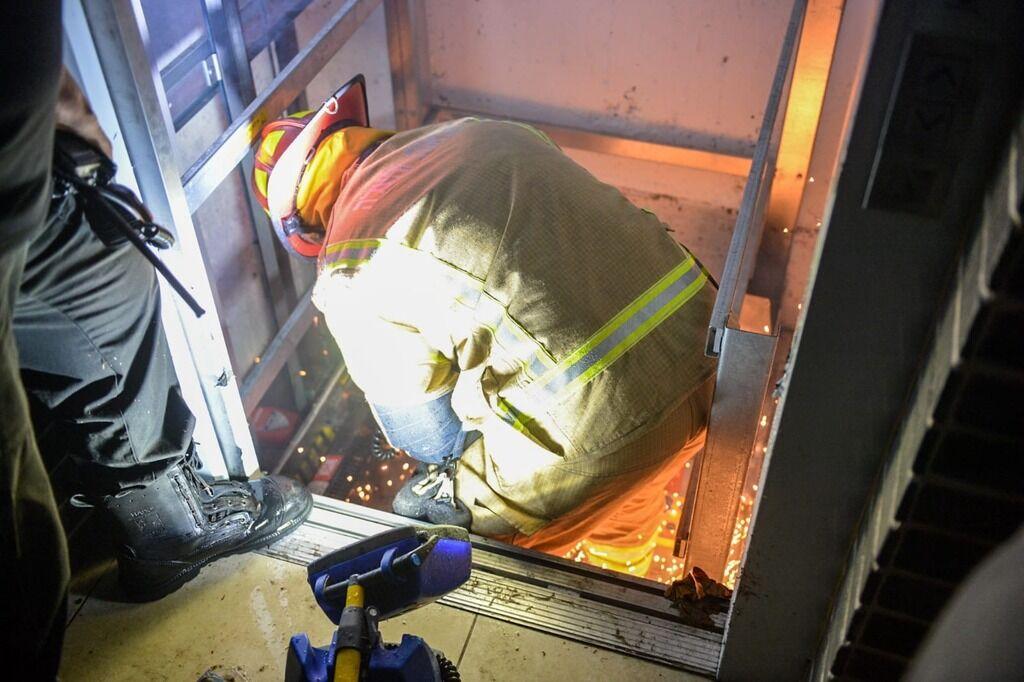 Пожарные работают над извлечением людей из лифта