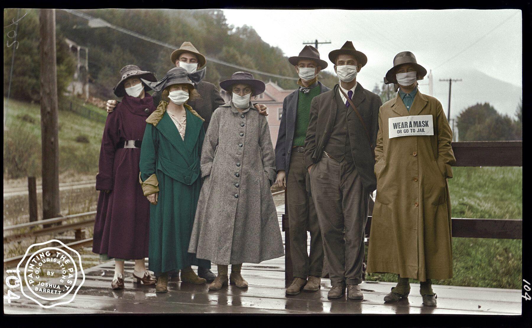 """Группа молодых людей сфотографировалась на железнодорожном вокзале в Милл-Валли, Калифорния (США), 1918 год. У женщины справа на шее табличка, которая гласит: """"Носите маску или посадят в тюрьму"""""""