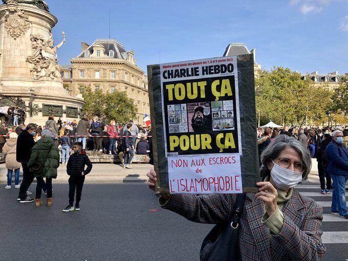 """Женщина держит плакат: """"Нет проходимцам исламофобии"""""""