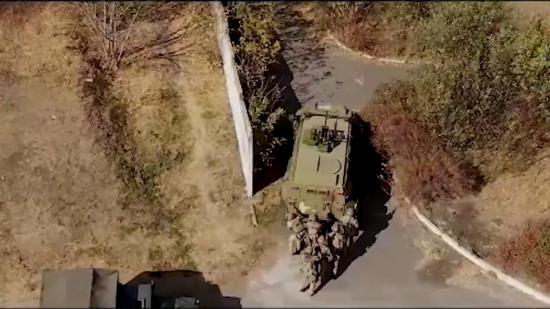 Украинские бойцы подходили к зданию позади военной техники, которая служила прикрытием