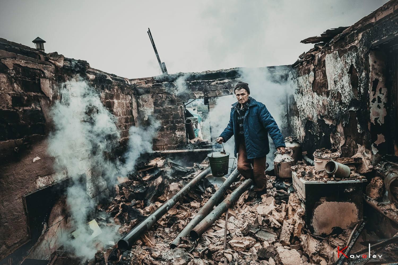 Мужчина тушит огонь с ведром.