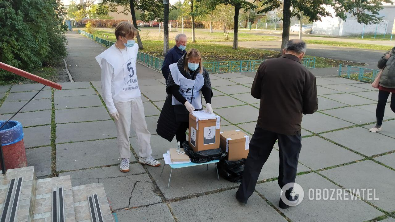 Волонтеры стоят возле избирательного участка.