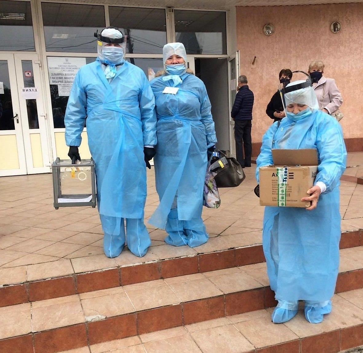 Члени виборчої комісії в захисних костюмах.