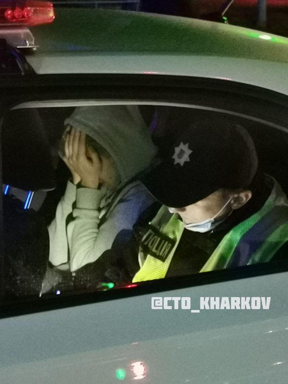 Дмитрий Кравченко в автомобиле полиции прикрыл лицо руками