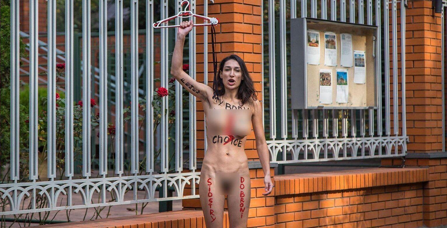 Активистка держала в руках вешалки под цвет польского флага